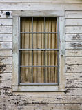 Old Window. In peeling and yellowing wood siding wall Royalty Free Stock Image