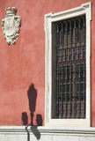 Old window and antique shield in a red facade. Seville, Spain Royalty Free Stock Photos