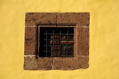 Old window with bars. Old window on yellow wall Stock Image