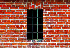 Old window with bars in brick wall Royalty Free Stock Photography