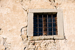 Old window with bars in decayed stone wall. Old window with bars in weathered decayed stone wall Royalty Free Stock Images