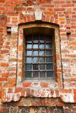 Old window with bars in a red brick Stock Image