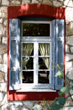 Old window with blue shutters and  curtains Stock Photo