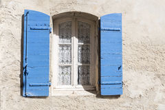 Old window with blue shutters and lace curtain in a rough-plaste Stock Image