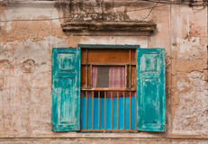 Old window with blue shutters. Royalty Free Stock Image