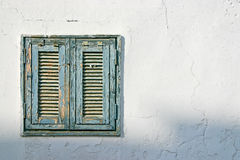 The old window with blue shutters on a white wall Stock Photography