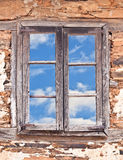 Old Window and Blue Sky. Old wooden window to blue sky with clouds Stock Photo