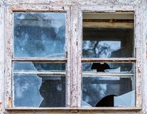 Old window with broken glass. The old window of an abandoned house with shabby paint and dirty, broken glass Royalty Free Stock Photo