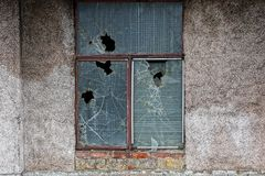 Old window with broken glass on a gray wall. Old window with broken glass on the gray wall of the building Stock Photo