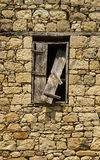 Old window with broken wooden shutter on a stone building Royalty Free Stock Image