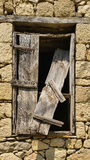 Old window with broken wooden shutter on a stone building Stock Photography