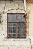 Old window on old building facade, with decorative brick frame. And arch and chimney coming out from window frame Stock Photography