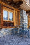 Old window, chairs and table. In front of a traditional cottage in the french alps Stock Photography