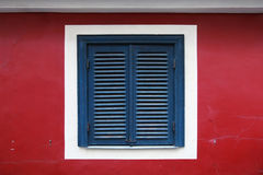 Old window with closed blue jalousies Royalty Free Stock Photography