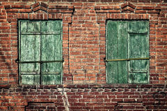 Old window with closed shutters on a brick wall Stock Photography