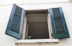 Old window with closed shutters on the window sill on the stone wall. Italian Village Royalty Free Stock Photo