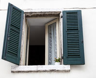 Old window with closed shutters on the window sill on the stone wall. Italian Village Royalty Free Stock Image