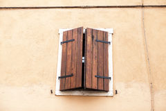 Old window with closed shutters on the window sill on the stone wall. Italian Village Stock Photo