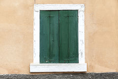 Old window with closed shutters on the window sill on the stone wall. Italian Village Stock Images