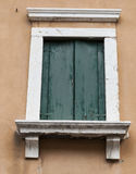 Old window with closed shutters on the window sill on the stone wall. Italian Village Stock Photos