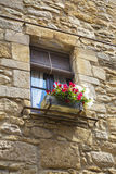 Old window on a cobble stone wall and decoration flowers pot Stock Photos