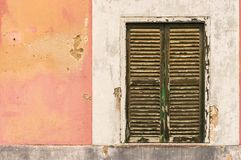 Old window and colored damaged plaster wall of vintage house Royalty Free Stock Images