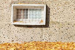 Old window on concrete stony wall with autumnal leaves Stock Photography