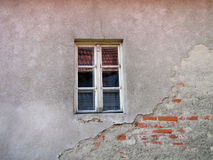 Old window on the damaged brick wall with cracks Stock Photo