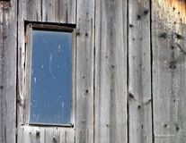 Old window on the damaged wooden roof Stock Photos