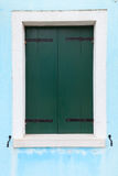 Old window with dark green shutters on light blue wall Royalty Free Stock Photography