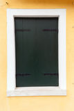 Old window with dark green shutters on light yellow wall Royalty Free Stock Image