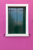 Old window with dark green shutters on pink (fucsia) wall Stock Photo