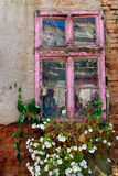 Old window. Decorated with flowers lies in the Nis street called sokace. Picture taken 15.08.2009 Royalty Free Stock Photo
