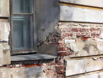 Old window in dilapidated stucco wall of building with red brick. S in deep fissures Stock Photography