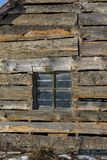 Old window frame in a vintage wooden wall in aold farm house. Old wooden wall with window detail of an old building in ruins. Royalty Free Stock Images