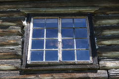 Old window with glass with a blue sky on the background of the wooden wall of the countryside log house Royalty Free Stock Images
