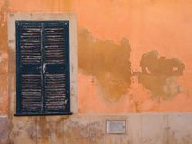 Old window with green painted closed wooden shutters on an orange Mediterranean ocher colored orange cracked peeling flaking wa. An old window with green painted royalty free stock photos