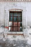 Old window with iron bars. Wooden window with dirty glasses and antique rusty grate with a torn net Stock Photography