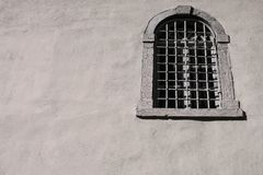 Old window with an iron lattice on a house facade Stock Photography