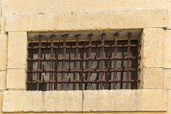 Old window and medieval castle. Old window in a medieval castle protected by a rusty iron grating with spikes Stock Photo