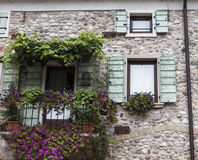 Old window with open shutters with flowers on the window sill on the stone wall. Italian Village Stock Photo