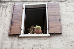 Old window with open shutters with flowers on the window sill on the stone wall. Italian Village Royalty Free Stock Photography
