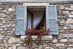 Old window with open shutters with flowers on the window sill on the stone wall. Italian Village Royalty Free Stock Images