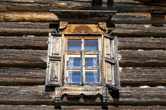 Old window with open shutters glass with a blue sky on the background of the wooden wall of the countryside log house Royalty Free Stock Photos