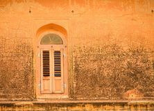 Old window in an orange wall. Stock Image