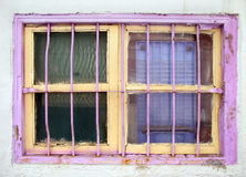 Old Window Painted Yellow and Pink. An old window with iron bars and painted in bright pink and yellow colors Stock Images