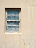 Old Window with Peeling Paint. Double hung window in a stucco building with weathered, peeling paint on the frame and sill Royalty Free Stock Images