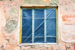 Old window with plastic membrane instead of glass. In messy wall Royalty Free Stock Image