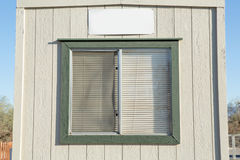 Old window with plastic window blinds with wood walls. Stock Photos