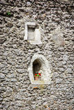 Old window with potted red flowers. Architectural detail. Vertical composition Royalty Free Stock Photos